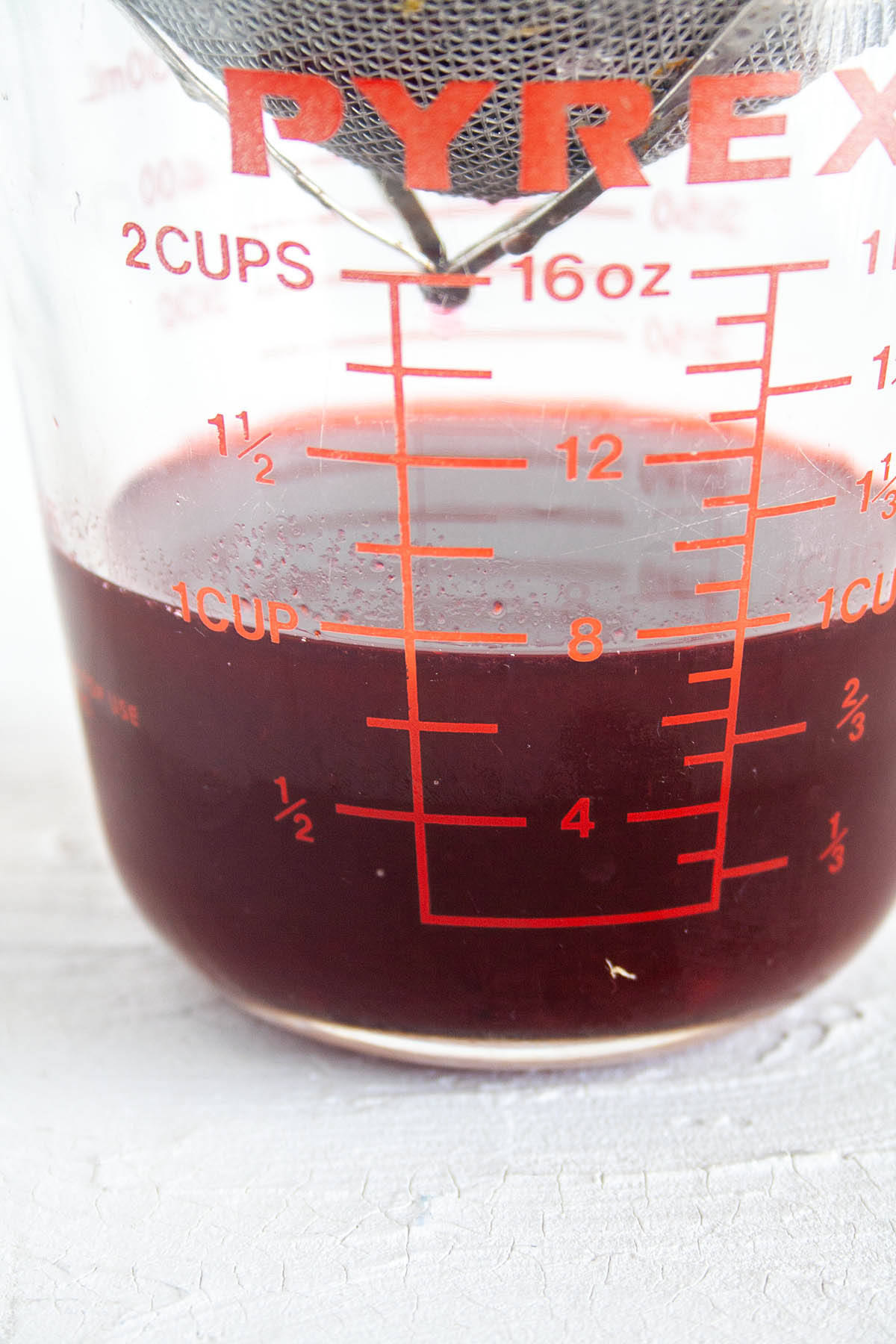 Blackberry Shrub in measuring cup with strainer above.