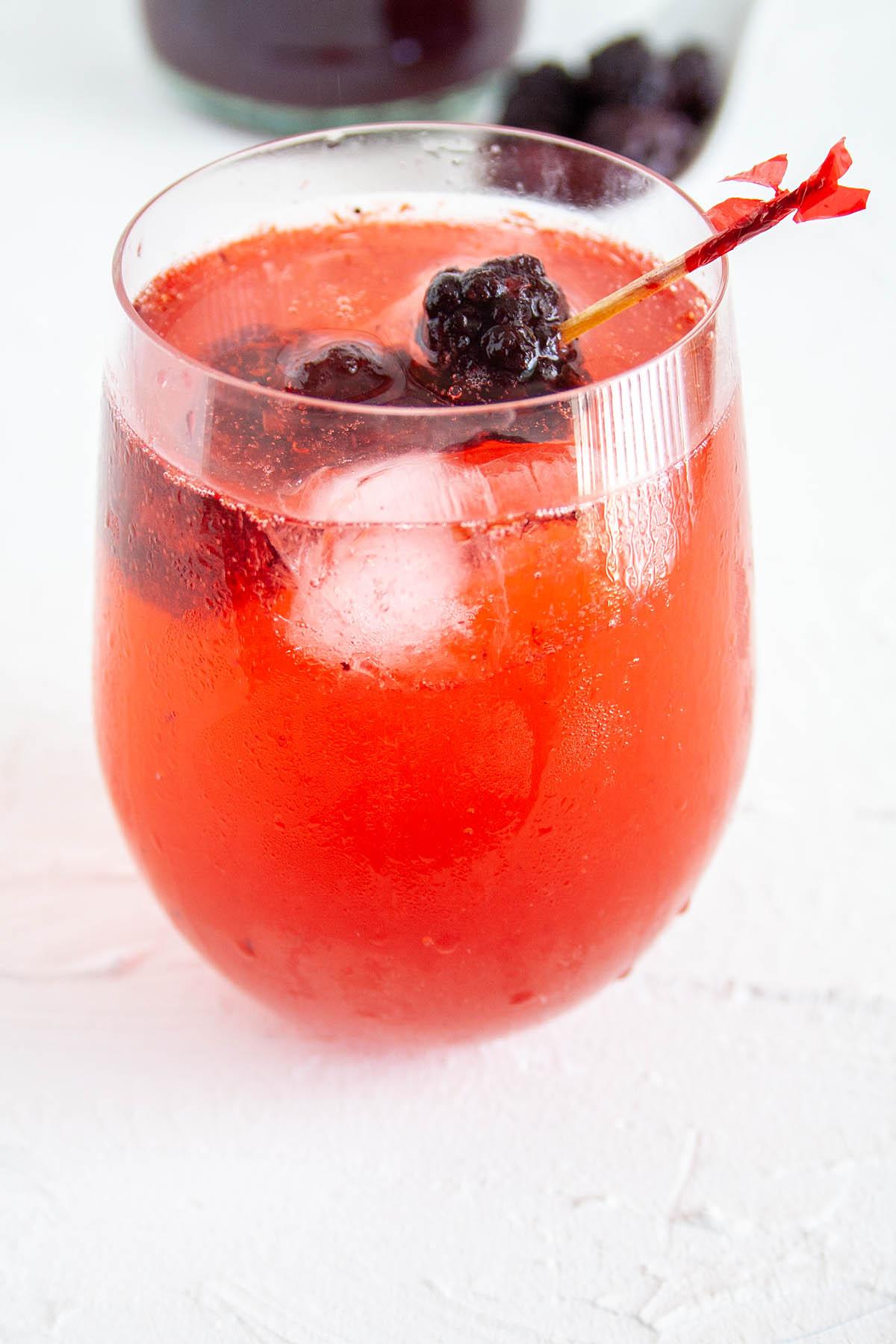Blackberry Shrub with club soda in wine glass.