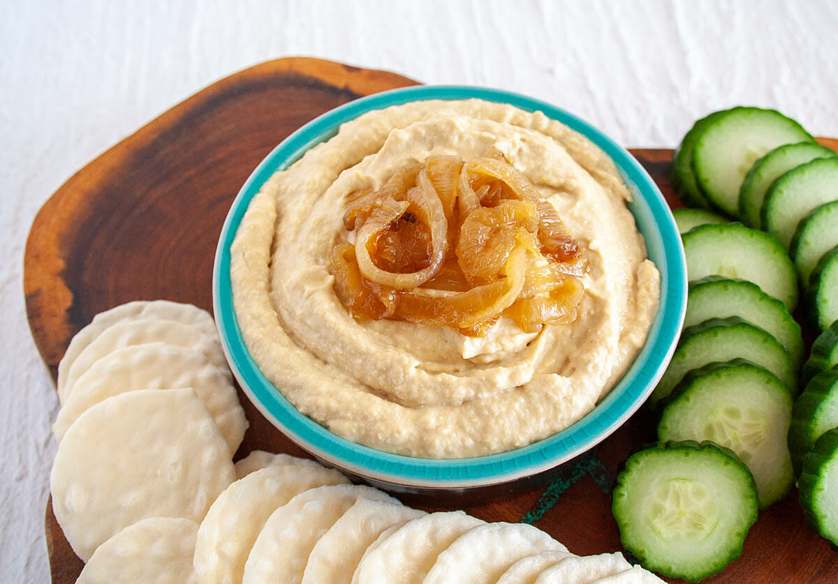 Caramelized Onion Hummus on cutting board with rice crackers and cucumber.