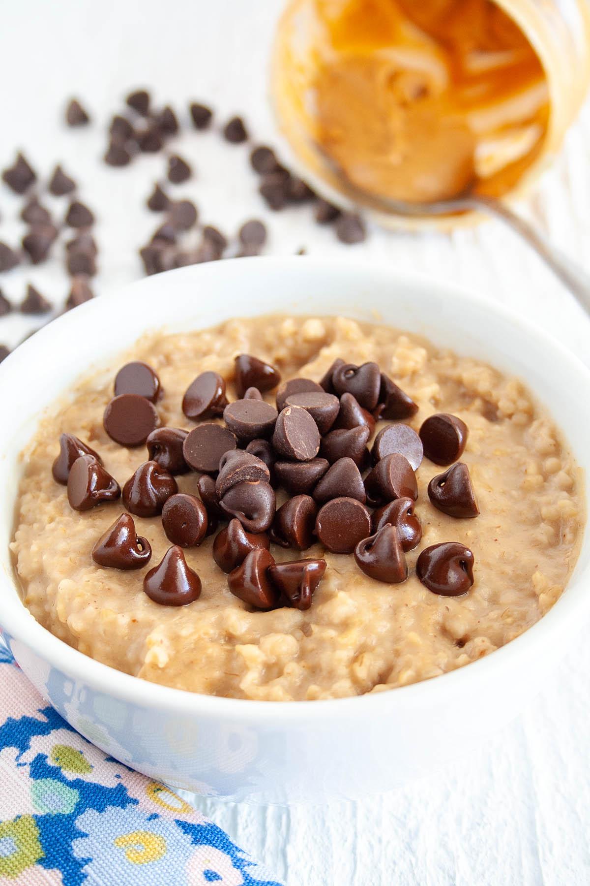 Peanut Butter Chocolate Chip Steel Cut Oats with peanut butter and chocolate chips in the background.