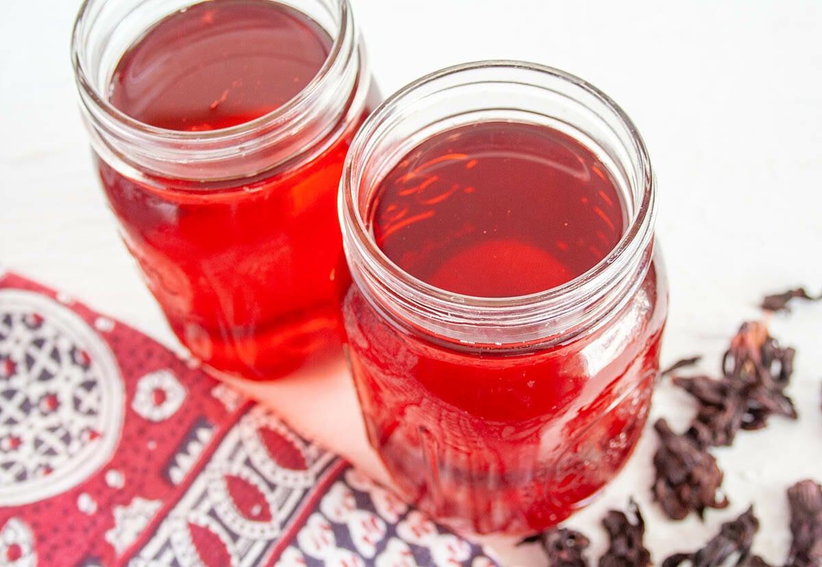 Hibiscus Kombucha in two mason jars.