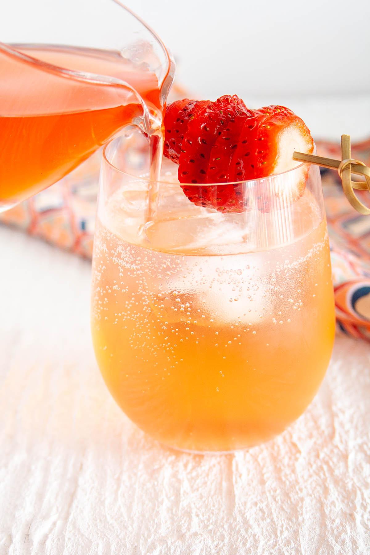 Strawberry Shrub being poured into glass with club soda.