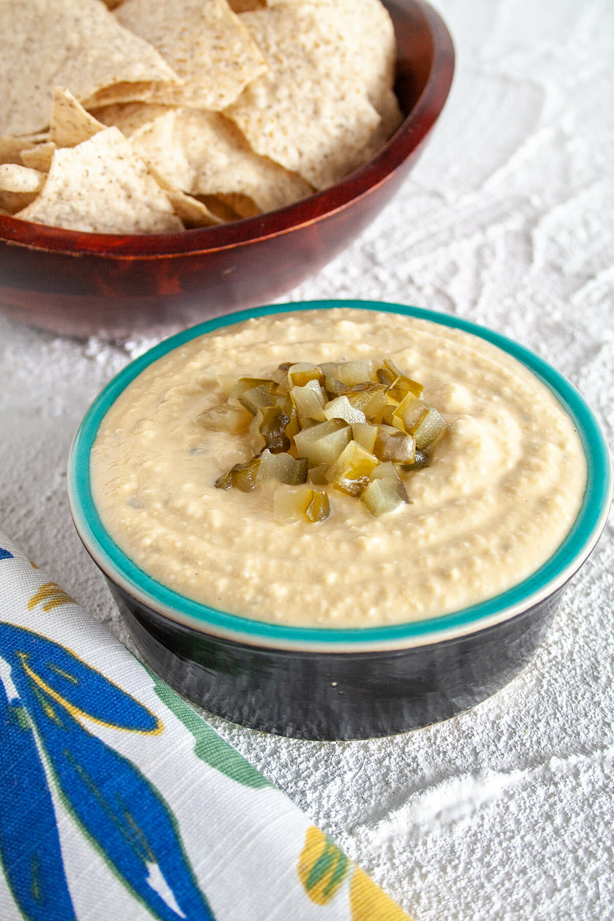 Dill Pickle Hummus with tortilla chips in background.