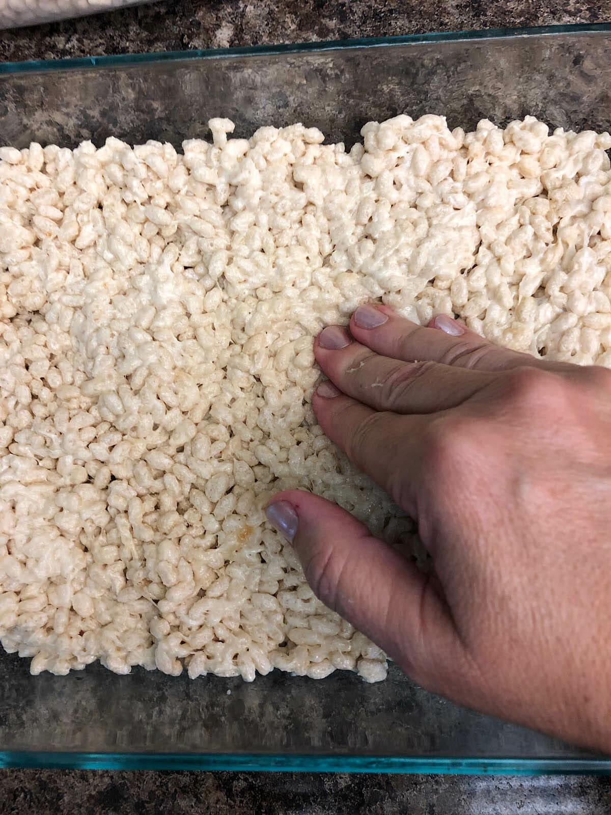 Vegan Rice Crispy Treats being pushed down in baking dish.