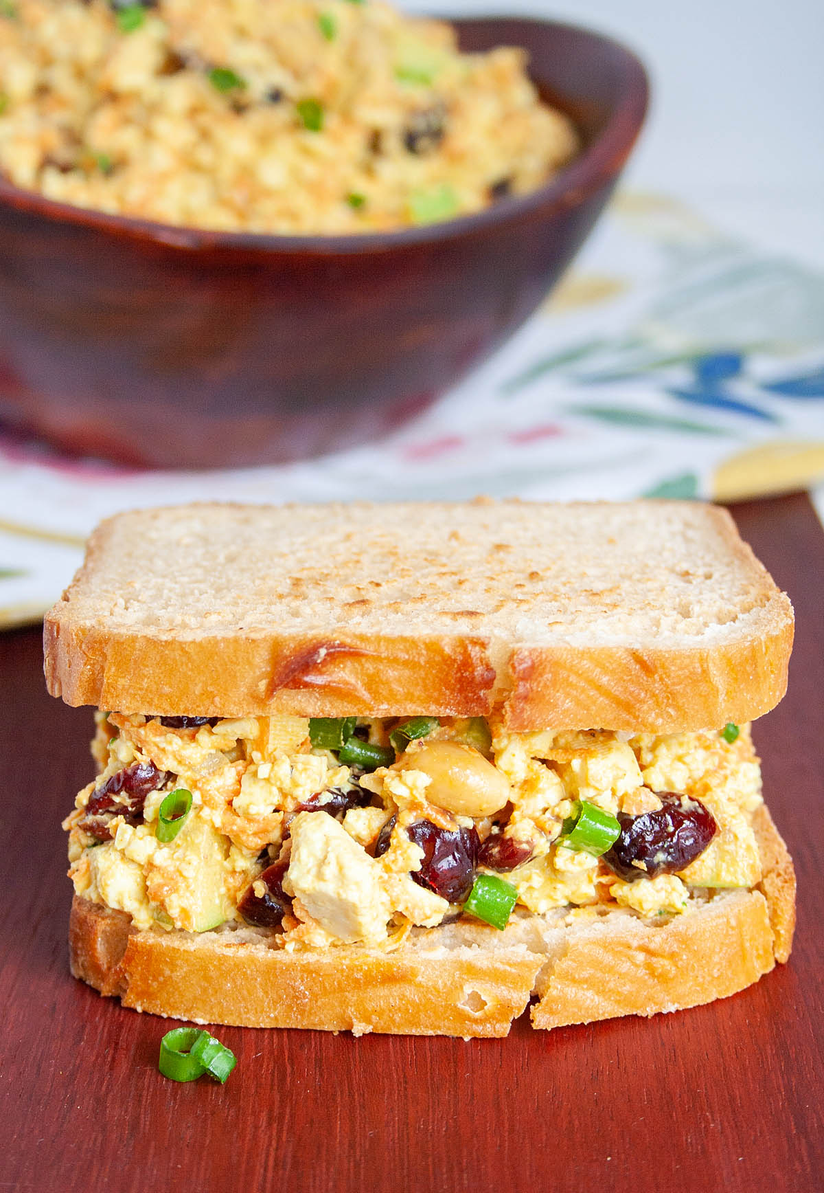 Curried Tofu Salad sandwich close up with a bowlful in background.
